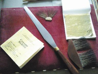 Инструментарий позолотчика: специальный нож для резки золота, замшевая подушка, на которой происходит вся предварительная обработка золота, «лапки»