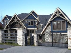 Цветовая схема этого дома довольно перегружена. И если камень фасада,и черепица крыши коррелируют с каменными столбиками забора, то синие вставки сайдинга - увы! - не гармонируют ни с чем